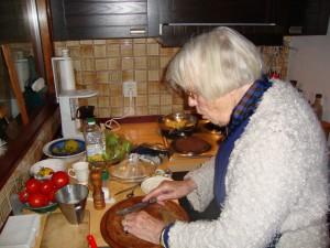 Mijn moeder in haar keukentje. Zij leert een technoloog graag een smakelijke en geurige tomatensoep te maken.