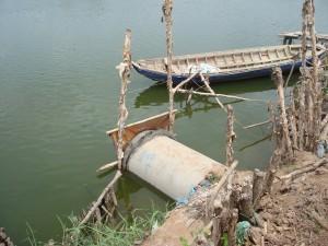 Mekongwater komt door deze buizen de vijver in. De vissen genieten van de restanten die hun soortgenoten bovenstrooms achter hebben gelaten.